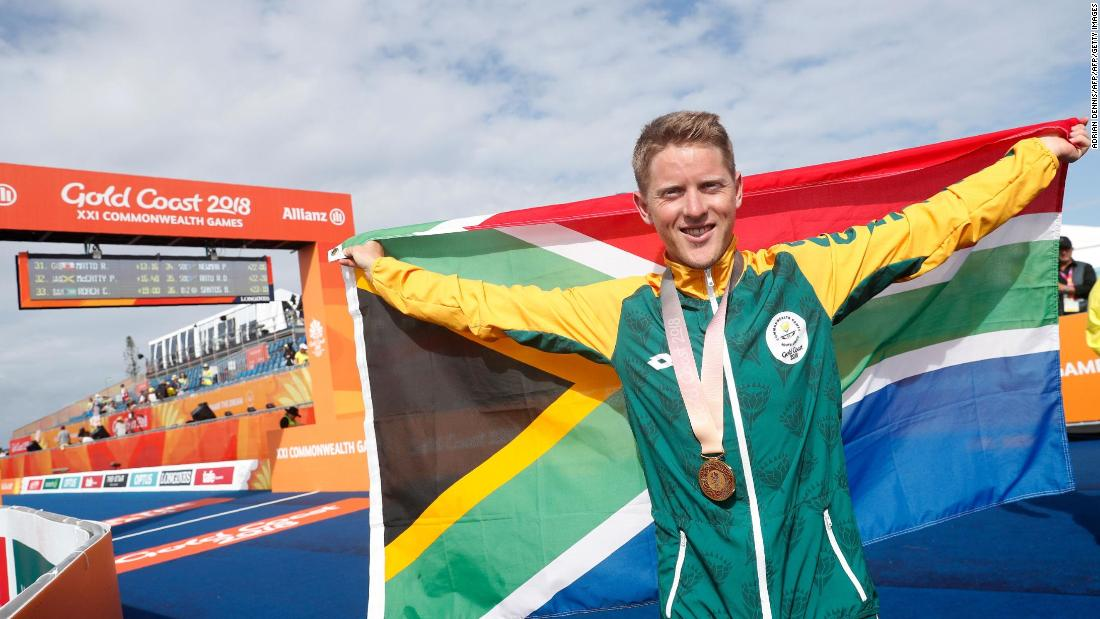 South Africa's Henri Schoeman poses with his country's flag after winning the men's triathlon final.
