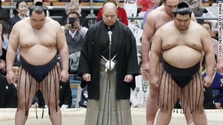 Japan Sumo Association Chairman Hakkaku, center, apologized after a referee ordered female medics to leave a sumo ring.