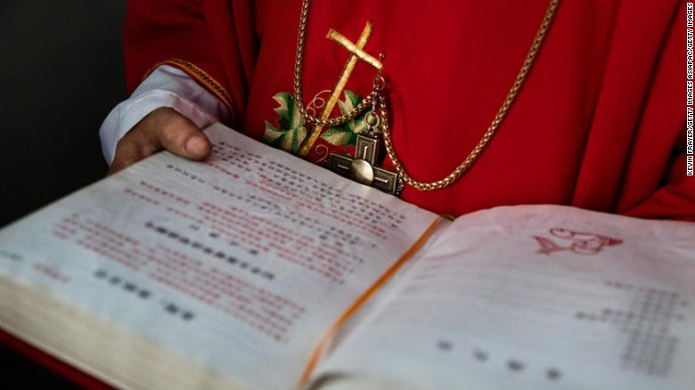 "A Chinese Catholic deacon holds a bible at the Palm Sunday Mass during Easter Holy Week at an ""underground"" church  on April 9, 2017 near Shijiazhuang, Hebei Province, China."