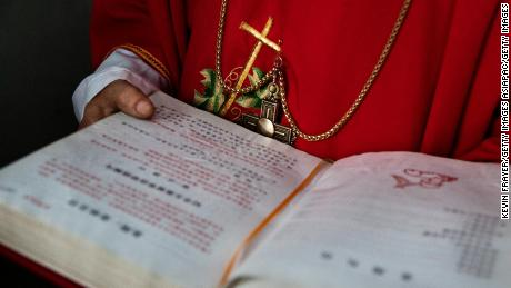 "SHIJIAZHUANG, CHINA - APRIL 09: (CHINA OUT) A Chinese Catholic deacon holds a bible at  the Palm Sunday Mass during the Easter Holy Week at an ""underground"" or ""unofficial"" church  on April 9, 2017 near Shijiazhuang, Hebei Province, China. China, an officially atheist country, places a number of restrictions on Christians, allowing legal practice of the faith only at state-approved churches. The policy has driven an increasing number of Christians and Christian converts 'underground' to secret congregations in private homes and other venues. While the size of the religious community is difficult to measure, studies estimate more than 80 million Christians inside China; some studies support the possibility it could become the most Christian nation in the world in the coming years. Officially there have been no relations between China and the Vatican since the country's modern founding in 1949 though in recent years there have been signs of warming relations between Chinese president Xi Jinping and Pope Francis that could possibly allow greater religious freedom in the future. At present, the split means approved Chinese Christians worship within a state-sanctioned Church known as the Patriotic Association which regards the Communist Party as its leader, not the Pope in Rome. (Photo by Kevin Frayer/Getty Images)"