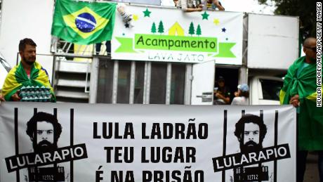 "Opponents of former Brazilian President (2003-2010) Luiz Inacio Lula da Silva, demonstrate at Barigui Park in Curitiba, where he is due to address a rally at the culmination of a campaign bus tour through southern Brazil on March 28, 2018.  Brazil's jittery presidential campaign entered disturbing new territory Wednesday after scandal-plagued leftist frontrunner Luiz Inacio Lula da Silva's bus convoy was shot at and his main rival branded him a ""scoundrel."" Despite the daunting legal situation, Lula is a runaway favorite in opinion polls, with around 35 percent of voter intentions, followed by Bolsonaro with around 17 percent.  / AFP PHOTO / Heuler Andrey        (Photo credit should read HEULER ANDREY/AFP/Getty Images)"