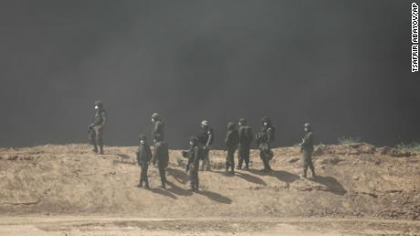 Israeli soldiers stand as smoke rises on protests on the border between Israel and Gaza on Friday