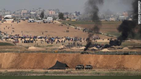Israeli soldiers are seen as Palestinians protest at the Israel-Gaza border on Friday.