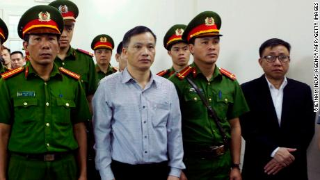 Vietnamese lawyer Nguyen Van Dai (center) stands in a courtroom during his trial with other political activists in Hanoi on April 5, 2018.