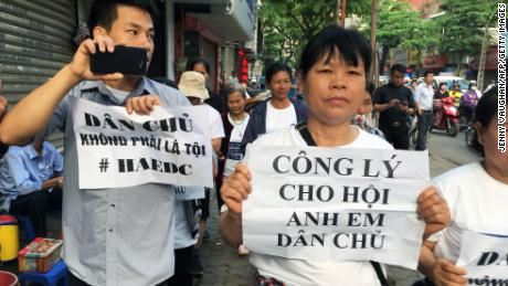 Protesters display placards as they march towards a courthouse during the trial of a prominent lawyer and five other activists in Hanoi on April 5.