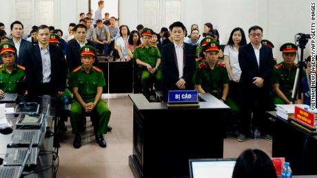 Lawyer Nguyen Van Dai (center) and other political activists stand in a courtroom during their trial in Hanoi on April 5.