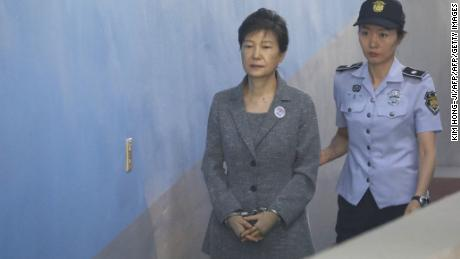 TOPSHOT - South Korean ousted leader Park Geun-hye (L) arrives at a court in Seoul on August 25, 2017. The heir to the Samsung business empire, including the world's biggest smartphone maker, awaited the verdict on August 25 in his corruption trial over the scandal that brought down South Korean president Park Geun-Hye. / AFP PHOTO / POOL / KIM HONG-JI        (Photo credit should read KIM HONG-JI/AFP/Getty Images)