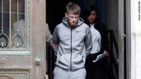 Mixed martial arts fighter Cian Cowley is led Friday morning from the NYPD's 78th precinct building.