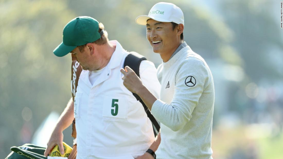 Haotong Li walks with caddie Michael Burrow on the first hole Friday.