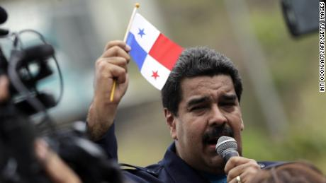 Venezuelan President Nicolas Maduro holds a Panamanian flag while he gives a speech during a visit at El Chorrillo neighborhood in Panama City on April 10, 2015. Regional leaders begin to arrive for a historic Summit of the Americas that will see the US and Cuban presidents sit face to face for the first time in decades.  AFP PHOTO / INTI OCON        (Photo credit should read Inti Ocon/AFP/Getty Images)