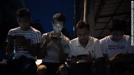 Young men browse Facebook on their smartphones as they sit in a street in Yangon.