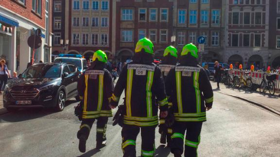 Firefighters walk in  downtown Muenster, Germany, Saturday, April 7, 2018. German news agency dpa says several people were  killed after car crashes into crowd in the city of Muenster