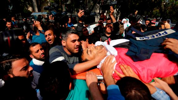Mourners carry the body of a Palestinian journalist during his funeral Saturday in Gaza City.