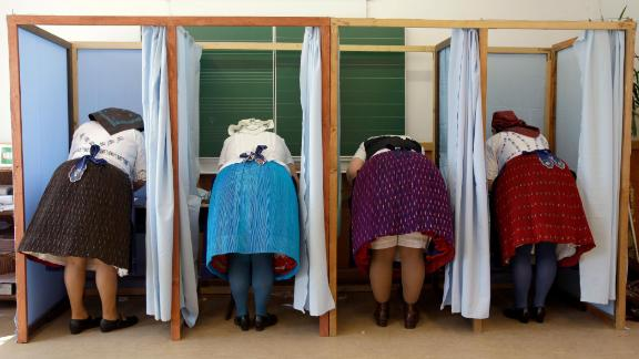 Women dressed in traditional Hungarian outfits cast their votes.