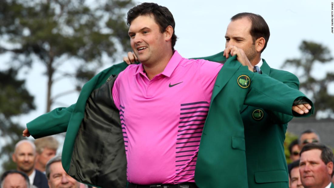 Patrick Reed is presented with the green jacket by Sergio Garcia during the green jacket ceremony on Sunday.