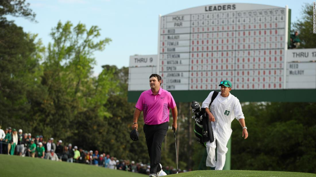 Patrick Reed walks onto the 18th green with caddie Kessler Karain during the final round on Sunday.
