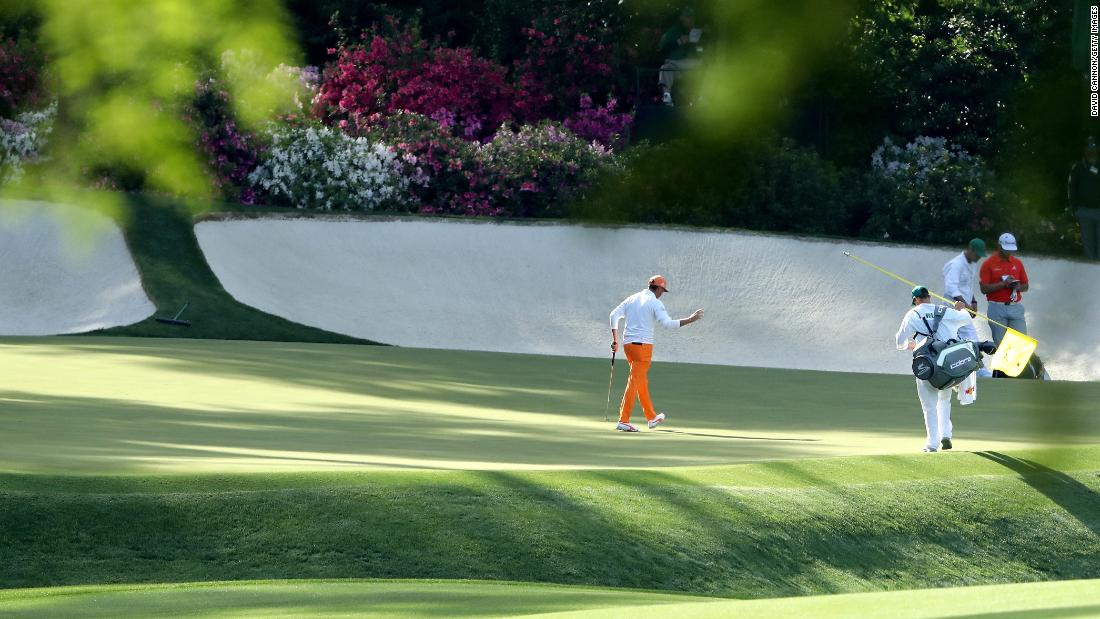 Rickie Fowler waves on the 13th green.