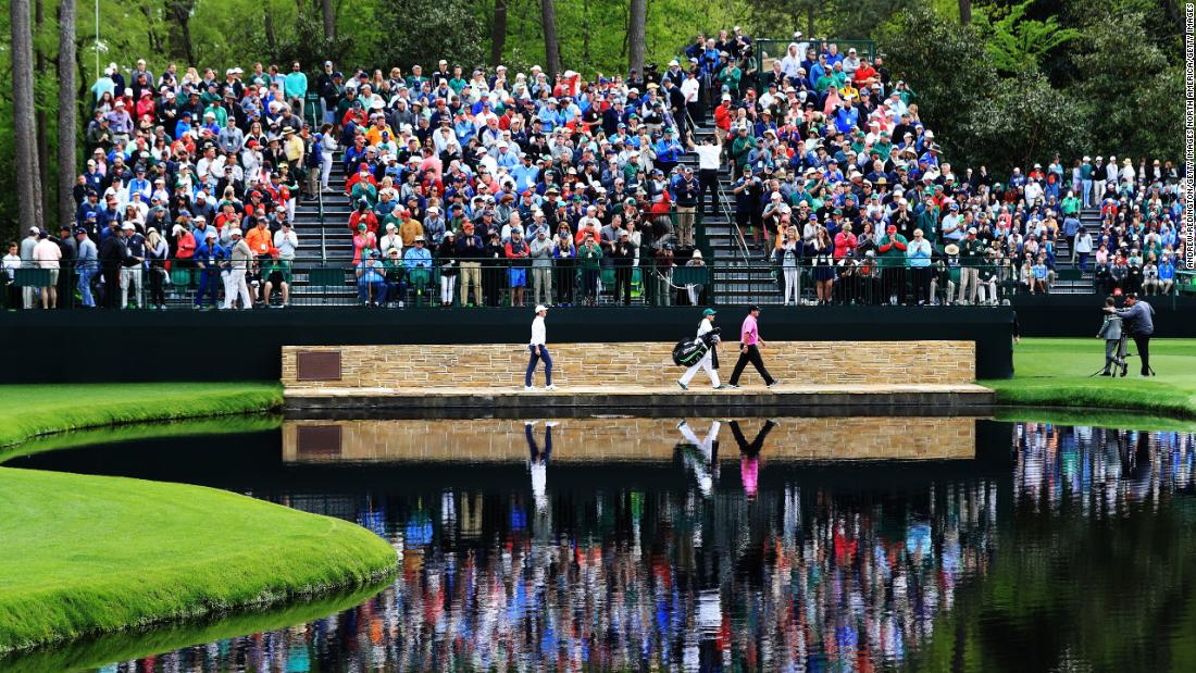 Patrick Reed of the United States, Rory McIlroy of Northern Ireland and caddie Kessler Karain cross the Sarazen Bridge on the 16th hole.