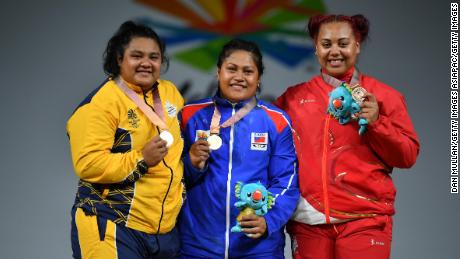 Silver medallist Charisma Amoe-Tarrant of Nauru, gold medallist Feagaiga Stowers of Samoa and bronze medallist Emily Campbell of England pose on the podium for the women's 90/+90kg weightlifting final at the Commonwealth Games.