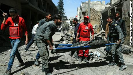 EDITORS NOTE: Graphic content / Members of the Syrian Civil Defence (known as the White Helmets) and the Red Crescent remove the body of a civilian from the street following air strikes on Douma, the main town of Syria's rebel enclave of Eastern Ghouta on March 20, 2018.   / AFP PHOTO / HASAN MOHAMED        (Photo credit should read HASAN MOHAMED/AFP/Getty Images)