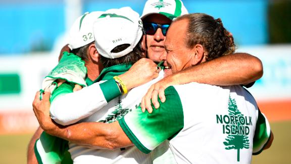 The Norfolk Island three-man lawn bowls team celebrate winning an historic bronze medal at the 2018 Commonwealth Games.