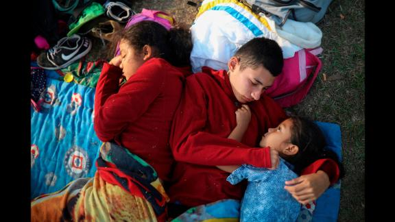 The Zelaya siblings -- from left, Daniela, Anderson and Nayeli -- huddle together on a soccer field in Matias Romero on Wednesday, April 4. Their father, Elmer, said the family is awaiting temporary transit visas that would allow them to continue to the US border, where they hope to request asylum and join relatives in New York. Related story: These are the migrants crossing Mexico