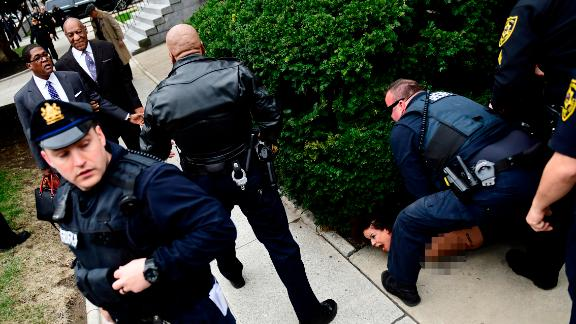 EDS NOTE: NUDITY - A protester is detained as Bill Cosby arrives for his sexual assault trial at the Montgomery County Courthouse, Monday, April 9, 2018, in Norristown, Pa. (AP Photo/Corey Perrine)