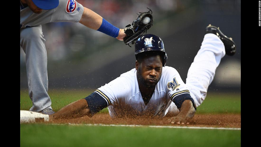 Milwaukee's Lorenzo Cain is tagged out at first base by the Chicago Cubs' Victor Caratini on Sunday, April 8.