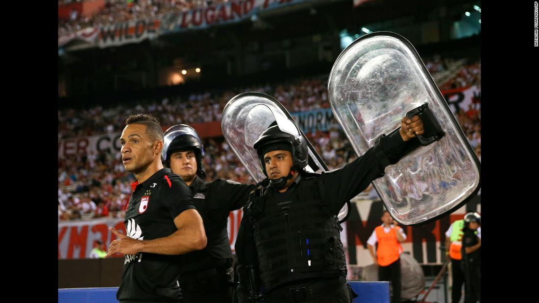 Police hold up shields near Anderson Plata, protecting the Santa Fe player from possible projectiles, as he takes a corner kick against River Plate on Thursday, April 5. The match in Buenos Aires ended scoreless.