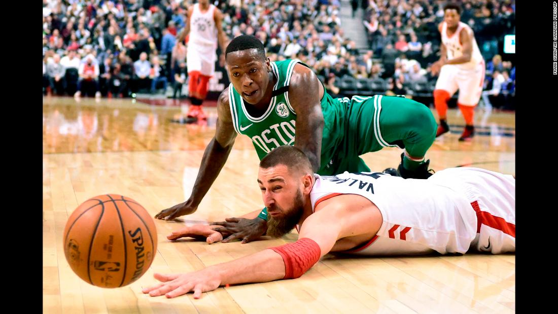 Boston's Terry Rozier, top, and Toronto's Jonas Valanciunas watch the ball get away from them during an NBA game on Wednesday, April 4.
