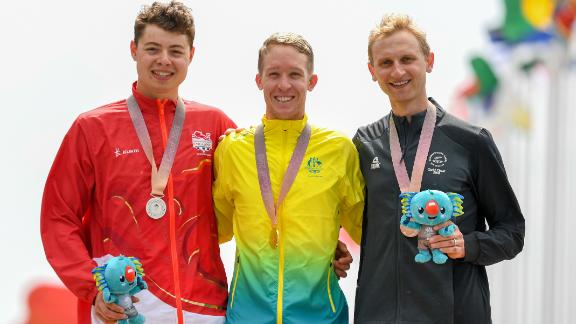 Bond (R) stands on the Gold Coast podium alongside Australia's Cameron Meyer and England's Harry Tanfield.