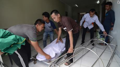 In this Monday, April 9, 2018, photo, family move the body of a victim who died from drinking poisonous bootleg liquor at a hospital in Cicalengka, West Java, Indonesia. Indonesian authorities say more people have died from toxic bootleg liquor, raising the toll this month to nearly 80 and highlighting how attempts to curb legal alcohol appear to have tragically backfired. (AP Photo)