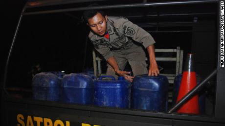Indonesian police prepare to transport containers filled with illegal alcohol from a house in Cicalengka district in West Java province on Sunday.