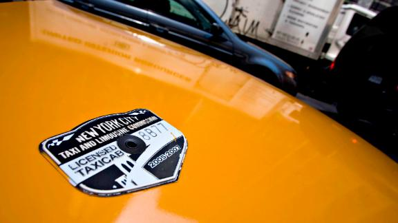 A New York City Taxi and Limousine Commission medallion sits on the hood of a taxi.