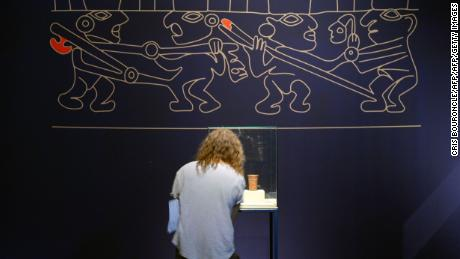 A visitor stands under a copy of a funeral chamber wall drawing while looking at objects under a glass box on display at the Art Museum of Lima (MALI) on June 11, 2014, part of an exhibit that brings together a representative selection of the pieces recovered from a noblewomans funerary chamber of the Castillo (Castle) of Huarmey, belonging to the pre-Inca Wari Culture (600-1000 BC), in central coastal Peru, 276 kilometers north of Lima, from an excavation initiated in 2012. From this discovery, scientists can address themes related the status and power of the elites, the relationship between women of the time and textile production, and the technologies used in metal, ceramics and woodworking. AFP PHOTO/CRIS BOURONCLE        (Photo credit should read CRIS BOURONCLE/AFP/Getty Images)