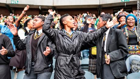 South African students sing and dance with other mourners at the memorial service.