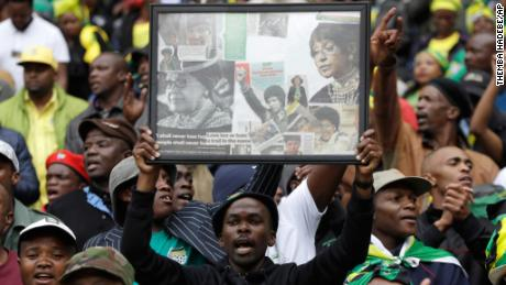 A man holds a frame showing newspaper clippings of Madikizela-Mandela during a memorial service in Soweto on Wednesday, three days before the funeral.