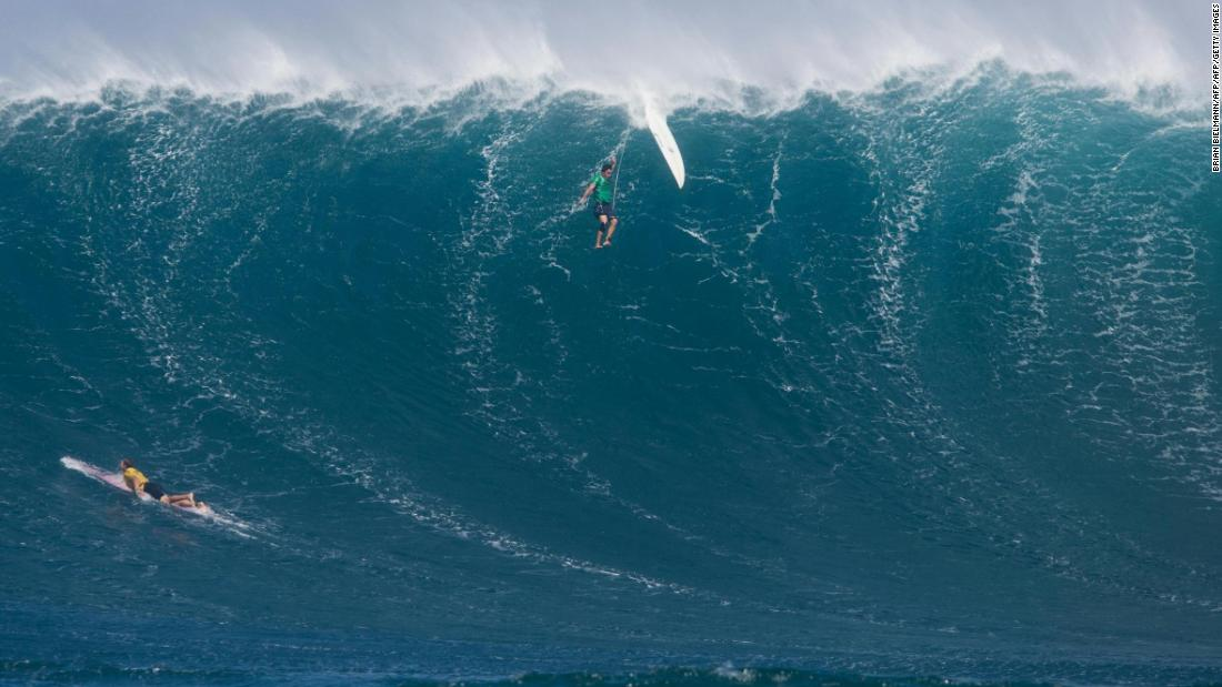 Another surfer is eaten up by a big wave as another one paddles to escape it.