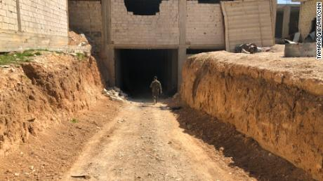 A Syrian government solider walks to an underground rebels' warehouse.