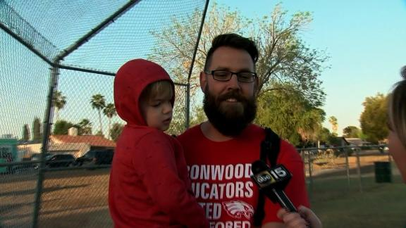 Justin McLellan holds one of his children at Wednesday's rally.