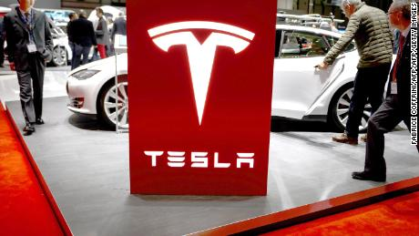 Visitor are seen at the booth of US electric carmaker Tesla Motors, during the press day of the Geneva Car Show on March 4, 2015 in Geneva.  AFP PHOTO / FABRICE COFFRINI        (Photo credit should read FABRICE COFFRINI/AFP/Getty Images)