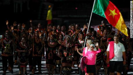 Cameroon's flagbearer Essiane Clotilde leads the delegation during the opening ceremony of the 2018 Gold Coast Commonwealth Games at the Carrara Stadium on the Gold Coast on April 4, 2018. / AFP PHOTO / Adrian DENNIS        (Photo credit should read ADRIAN DENNIS/AFP/Getty Images)