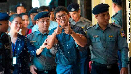 Detained Myanmar journalist Wa Lone, center, gives a thumbs up to reporters as he is escorted by police to a court for his ongoing trial in Yangon on April 11, 2018.