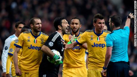 Juventus goalkeeper Buffon  argues with referee Michael Oliver following the award of a penalty to Real Madrid.