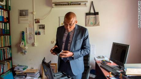Dr. Joseph Kamgno examines a new version of a cellphone-based microscope in his research facility in Yaoundé, Cameroon.