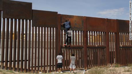 A young Mexican helps a compatriot to climb the metal wall that divides the border between Mexico and the United States to cross illegally to Sunland Park, from Ciudad Juarez, Chihuahua state, Mexico on April 6, 2018. 