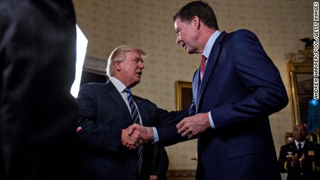 "WASHINGTON, DC - JANUARY 22: U.S. President Donald Trump (C) shakes hands with James Comey, director of the Federal Bureau of Investigation (FBI), during an Inaugural Law Enforcement Officers and First Responders Reception in the Blue Room of the White House on January 22, 2017 in Washington, DC. Trump today mocked protesters who gathered for large demonstrations across the U.S. and the world on Saturday to signal discontent with his leadership, but later offered a more conciliatory tone, saying he recognized such marches as a ""hallmark of our democracy."" (Photo by Andrew Harrer/Pool/Getty Images)"