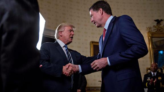 """WASHINGTON, DC - JANUARY 22: U.S. President Donald Trump (C) shakes hands with James Comey, director of the Federal Bureau of Investigation (FBI), during an Inaugural Law Enforcement Officers and First Responders Reception in the Blue Room of the White House on January 22, 2017 in Washington, DC. Trump today mocked protesters who gathered for large demonstrations across the U.S. and the world on Saturday to signal discontent with his leadership, but later offered a more conciliatory tone, saying he recognized such marches as a """"hallmark of our democracy."""" (Photo by Andrew Harrer/Pool/Getty Images)"""