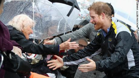 "Harry first met an Australian woman named Daphne Dunne on a trip to Sydney in 2015. Back in the city last June, Harry spotted the 97-year-old in the crowd, Jackson explains. ""It was the rainiest day, torrential,"" he recalls. ""He rushed over to her in the rain, arms outstretched, and hugged her. It was such a sweet moment... She'd been waiting all day for him."""