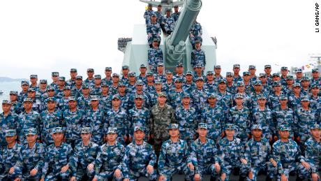 Chinese President Xi Jinping, center in green military uniform, poses with soldiers on a navy ship on April 12.